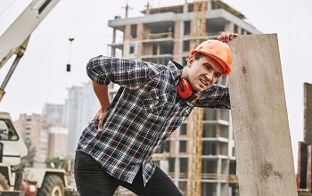 Hard work. Construction worker in protective helmet feeling back pain while working at construction site. Building construction. Pain concept. Dangerous job