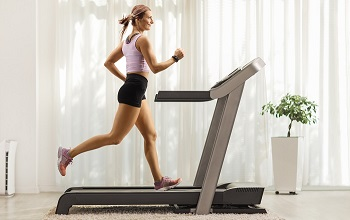 Full length profile shot of a fit woman running on a treadmill at home
